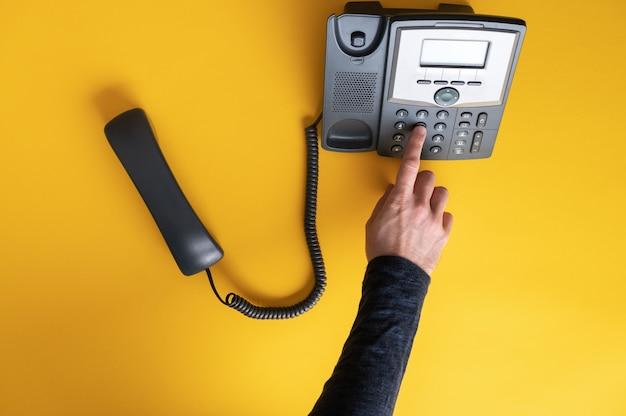 Vue de dessus d'un doigt masculin composant un numéro de téléphone à l'aide d'un téléphone fixe noir. sur fond jaune.