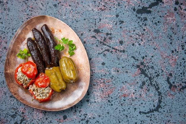 Vue de dessus dolma aubergine avec tomates cuites et poivrons remplis de viande hachée à l'intérieur de la plaque, plat de couleur alimentaire
