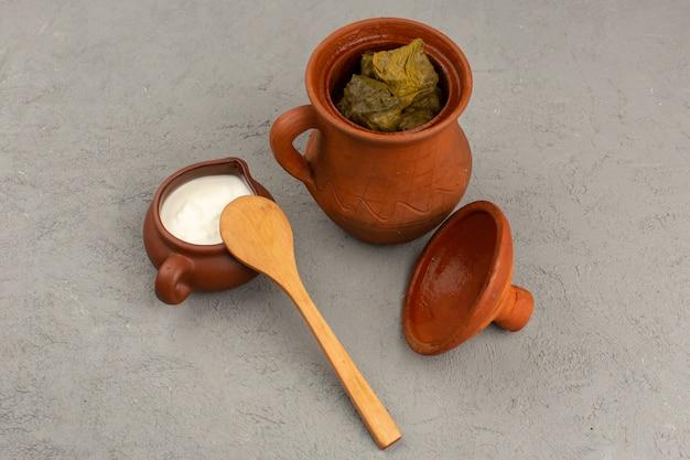 Vue de dessus dolma à l'intérieur du pot brun avec du yaourt sur le gris
