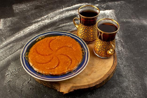 Une vue de dessus doux délicieux halva délicieux dessert sucré oriental à l'intérieur de la plaque avec du thé sur la surface sombre