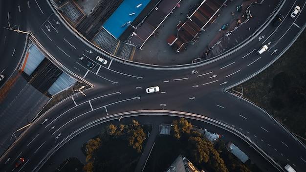 Vue de dessus d'un drone aérien sur une route goudronnée avec des voitures dans la ville du soir