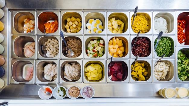 Vue de dessus du bar à salade avec assortiment d'ingrédients pour des repas sains et diététiques.