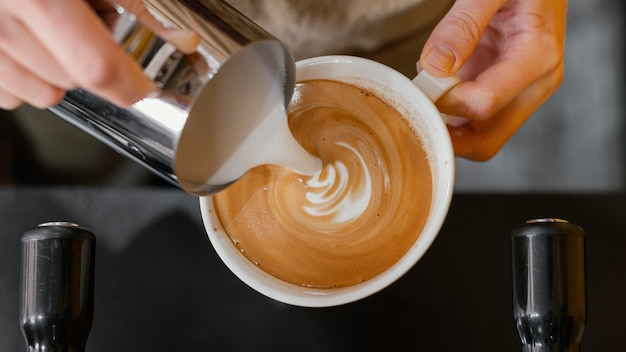Vue de dessus du barista masculin verser du lait dans des tasses à café