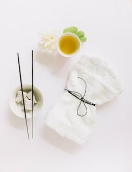 Vue de dessus du bâton d'encens; pierre ponce; fleur; feuille de gingko; huile et serviette attachée sur fond blanc