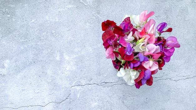 Vue de dessus du beau bouquet de fleurs de pois sucrés colorés sur une surface grunge
