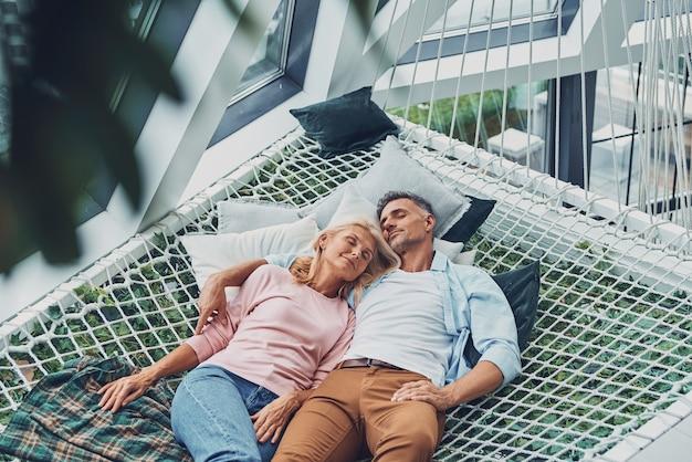 Vue de dessus du beau couple mature dormant en position couchée dans un grand hamac à la maison ensemble