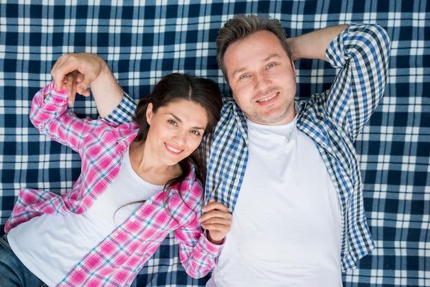 Vue de dessus du beau couple souriant allongé sur une couverture à carreaux bleu