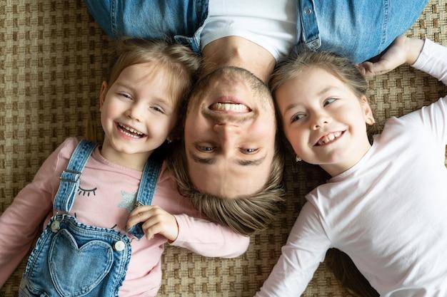 Vue de dessus du beau jeune père et de ses petites filles mignonnes regardant la caméra et souriant, allongé sur le sol.