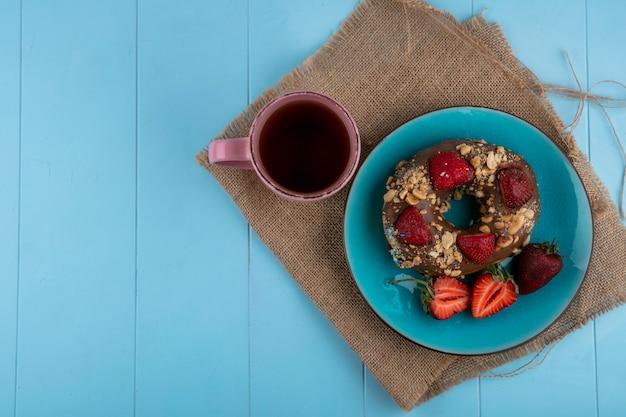 Vue de dessus du beignet au chocolat avec des fraises sur une plaque bleue avec une tasse de thé sur une serviette beige sur une surface bleue