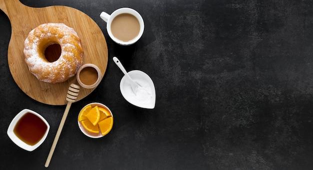 Vue de dessus du beignet sur une planche à découper avec du miel et du café