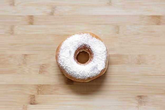 Vue de dessus du beignet saupoudré de poudre blanche sur table en bois.