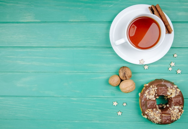 Vue de dessus du biscuit au chocolat et tasse de thé à la cannelle sur sachet de thé aux noix sur vert avec copie espace