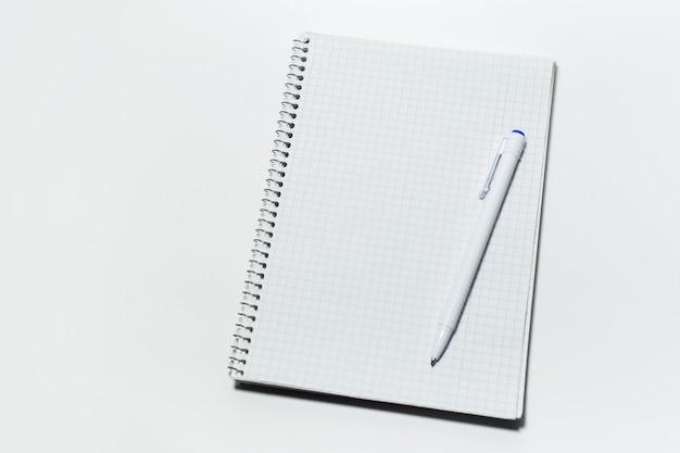 Vue de dessus du bloc-notes et du stylo sur blanc