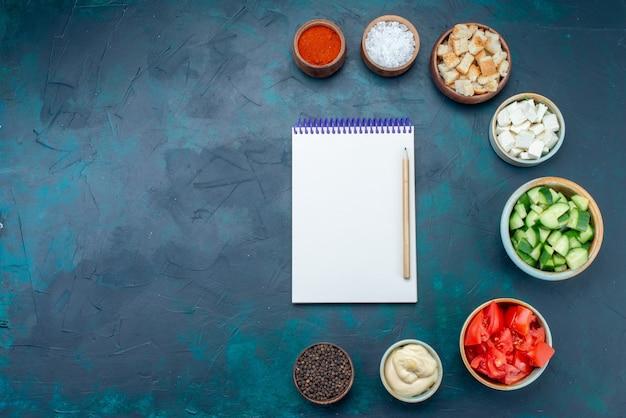 Vue de dessus du bloc-notes et des légumes avec des assaisonnements sur la couleur du repas de collation de nourriture végétale fond bleu foncé