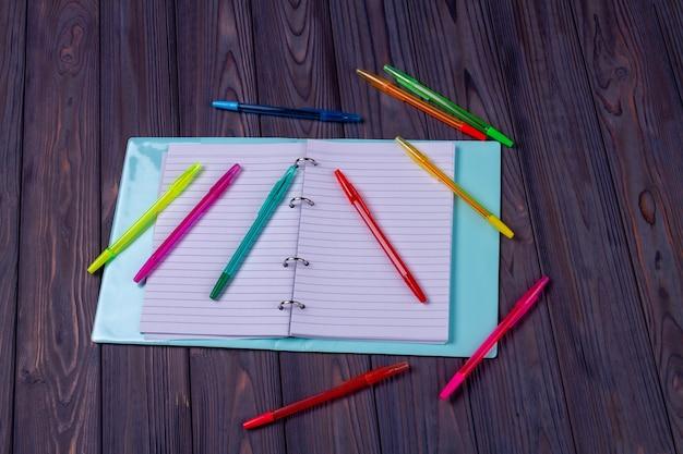 Vue de dessus du bloc-notes ouvert avec de nombreux stylos. fond de bureau gris.