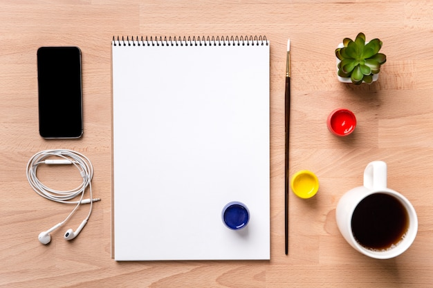 Vue de dessus du bloc-notes avec pages blanches, pinceau,