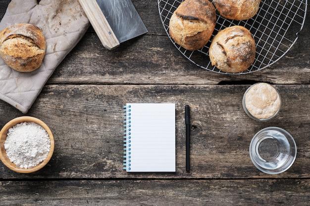 Vue de dessus du bloc-notes de recette vierge avec un marqueur noir à côté de petits pains