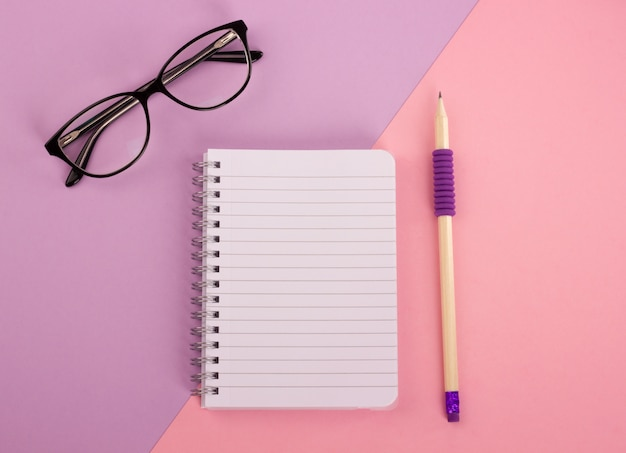 Vue de dessus du bloc-notes à spirale, crayon en bois et lunettes sur fond rose-lavande. plat la