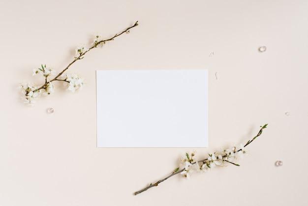 Vue de dessus du bloc-notes vierge parmi les fleurs de pomme de printemps isolées sur fond beige clair