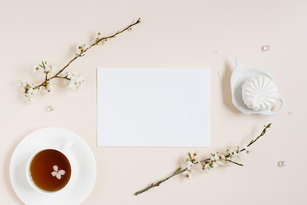 Vue de dessus du bloc-notes vierge parmi les fleurs de pomme de printemps et une tasse de thé