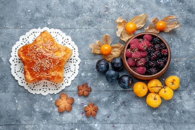 Vue de dessus du bol avec des baies fruits mûrs frais avec une pâtisserie sucrée sur gris, berry fruit frais forêt douce