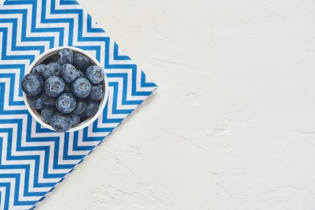 Vue de dessus du bol avec des bleuets sur textile bleu et béton blanc