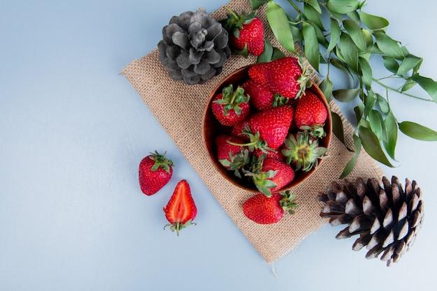 Vue de dessus du bol de fraises avec des pommes de pin sur un sac sur une surface blanche décorée de feuilles avec copie espace