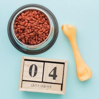 Vue de dessus du bol de nourriture avec calendrier et os pour la journée des animaux