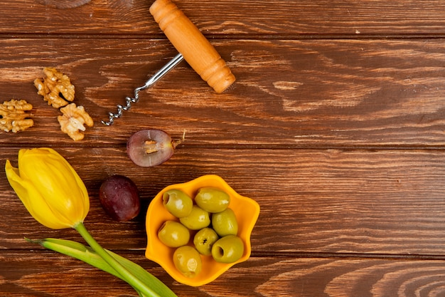 Vue de dessus du bol d'olive avec tire-bouchon raisin noyer et fleur sur fond en bois avec copie espace