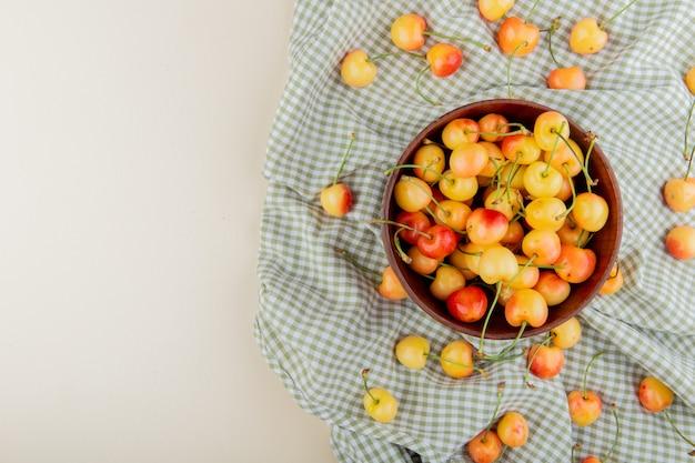 Vue de dessus du bol plein de cerises jaunes et rouges sur un tissu écossais sur le côté droit et une surface blanche avec copie espace