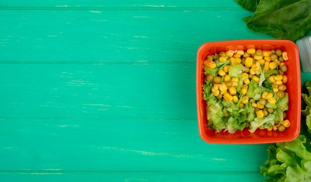Vue de dessus du bol de pois jaunes avec de la laitue en tranches et des épinards de laitue entière sur le côté droit et la surface verte avec copie espace