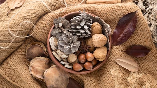 Vue de dessus du bol avec des pommes de pin et des noix sur la toile de jute