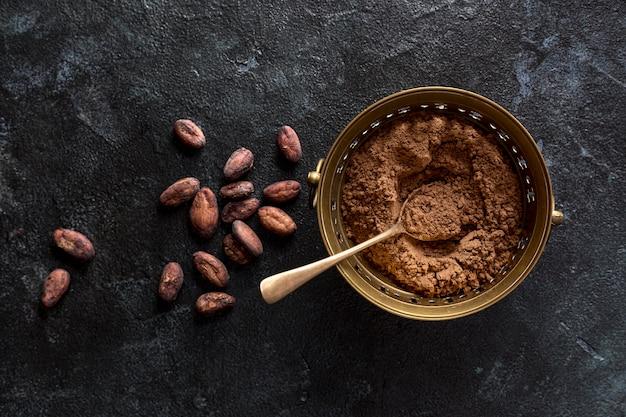Vue de dessus du bol avec de la poudre de cacao et des fèves de cacao