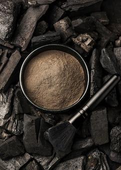 Vue de dessus du bol avec poudre fine et charbon de bois