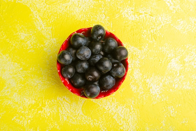 Vue de dessus du bol avec prunellier isolé sur la surface jaune