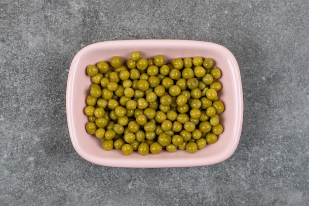 Vue de dessus du bol rose plein de pois verts en conserve