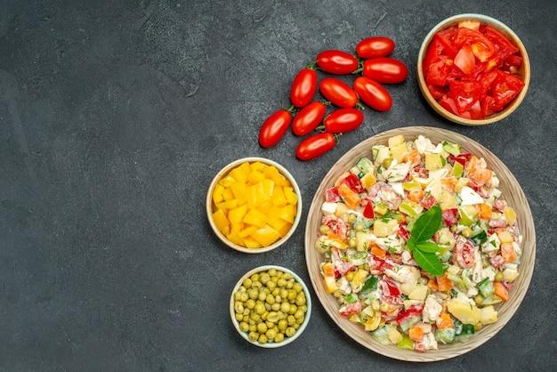 Vue de dessus du bol de salade de légumes aux légumes sur table gris foncé
