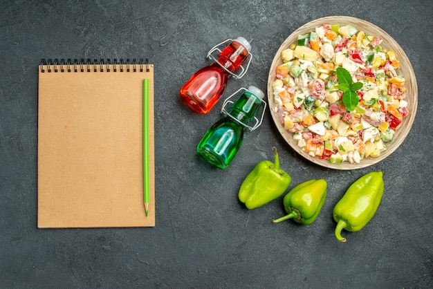 Vue de dessus du bol de salade de légumes avec bloc-notes de poivrons et bouteilles d'huile et de vinaigre sur la table vert foncé