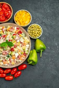 Vue de dessus du bol de salade de légumes avec des légumes sur le côté sur fond gris foncé