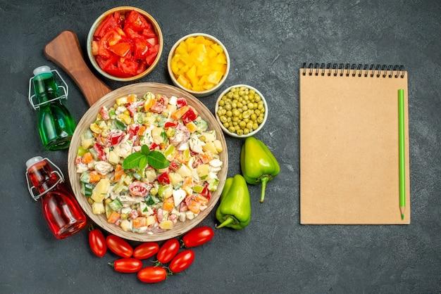 Vue de dessus du bol de salade de légumes sur le support de plaque avec des légumes et des bouteilles d'huile et de vinaigre et bloc-notes sur le côté et placez votre texte sur fond gris foncé