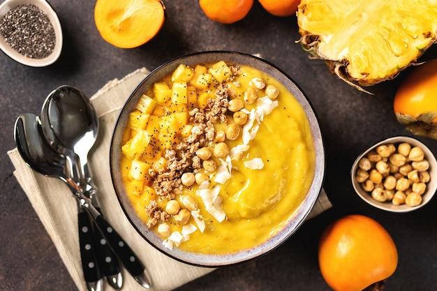 Vue de dessus du bol de smoothie à la mangue avec des fruits