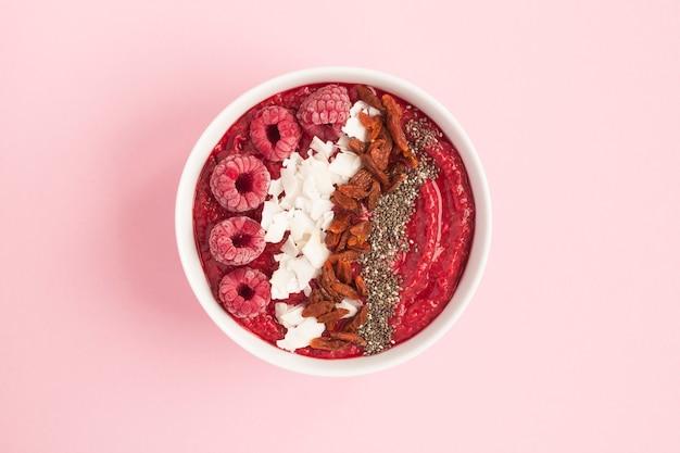 Vue de dessus du bol de smoothies aux framboises et superaliments naturels sur rose, vue du dessus