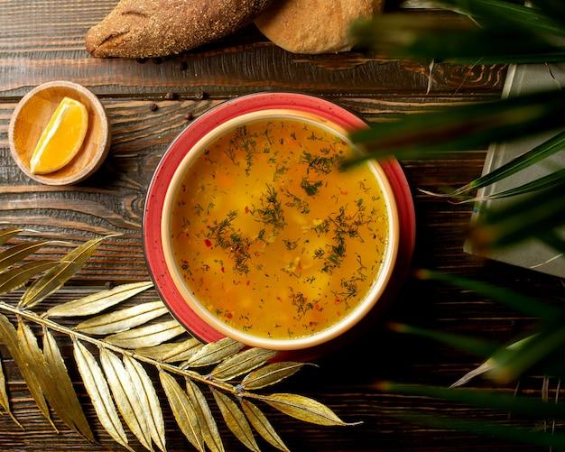 Vue de dessus du bol de soupe au poulet avec légumes et herbes