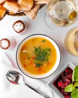 Vue de dessus du bol de soupe au poulet servi avec de la compote de feijoa et du pain