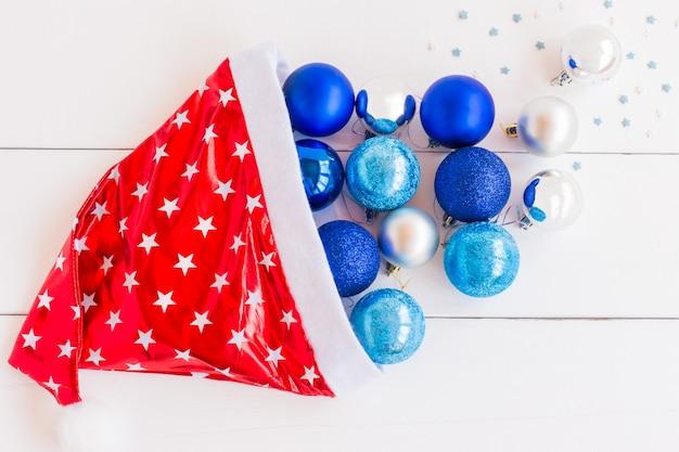 Vue de dessus du bonnet de père noël rouge et blanc avec des boules bleues et argentées éparses pour la décoration de l'arbre de noël. carte de voeux festive pour les vacances d'hiver