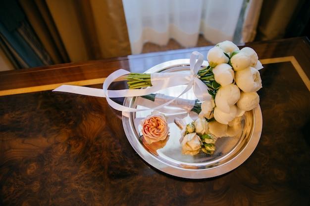 Vue de dessus du bouquet de mariée de fleurs blanches et ruban sur la plaque.