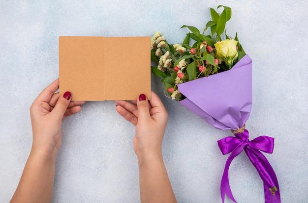 Vue de dessus du bouquet violet de rose avec des feuilles sur une surface blanche