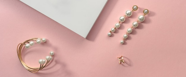 Vue de dessus du bracelet et des boucles d'oreilles en perles d'or sur une surface rose et blanche