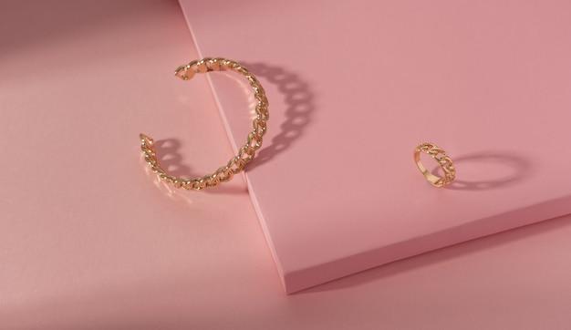 Vue de dessus du bracelet doré en forme de chaîne et de la bague sur papier rose