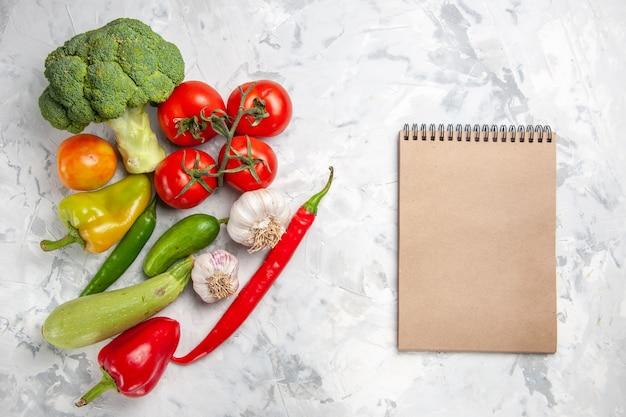 Vue de dessus du brocoli frais avec des légumes sur une salade de sol blanc régime santé mûr